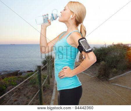 people, sport, fitness, jogging and technology concept - happy woman with smartphone and earphones listening to music and drinking water from bottle over beach sunset background