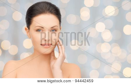beauty, people, holidays, luxury and health concept - beautiful young woman touching her face over lights background