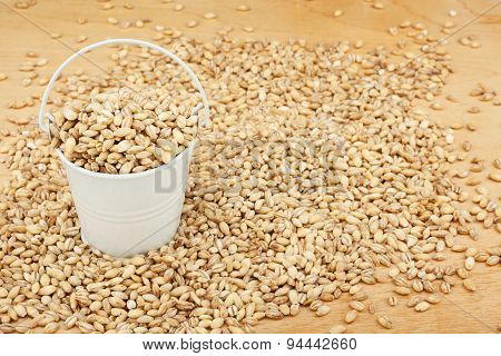 White Bucket With Pearl Barley On The Wooden Floor
