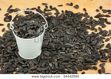 White Bucket With Sunflower Seeds  On The Wooden Floor