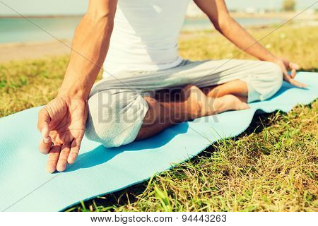fitness, sport, people and lifestyle concept - close up of man making yoga exercises on mat outdoors