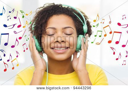 people, technology and leisure concept - happy african american young woman sitting on sofa with headphones listening to music over notes background