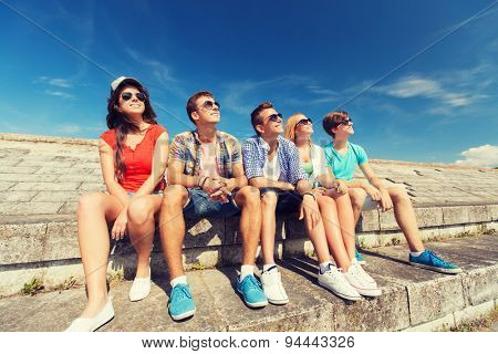 friendship, leisure, summer and people concept - group of smiling friends sitting on city street