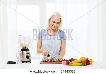 healthy eating, cooking, vegetarian food, dieting and people concept - smiling young woman with blender chopping fruits and berries for fruit shake at home