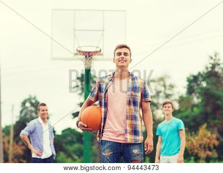 summer vacation, holidays, games and friendship concept - group of smiling teenagers playing basketball outdoors