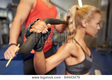 sport, fitness, teamwork and people concept - close up of young woman and personal trainer flexing muscles on cable gym machine