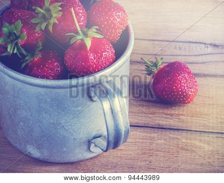 Ripe strawberries in a metal mug. Old wooden table.