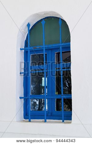 Traditional old blue painted greek window with bars