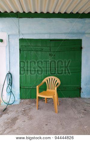 Yellow plastic chair in front of a green wooden door