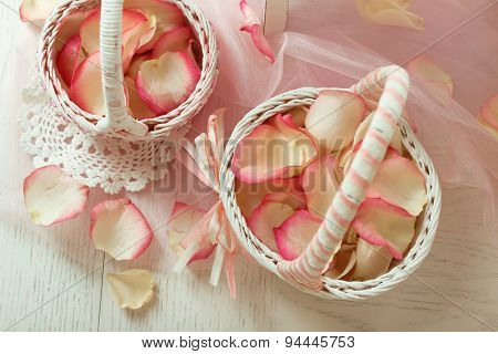 Wedding baskets with roses petals on table, on light background