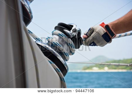 Winch And Sailors Hands On A Sailboat