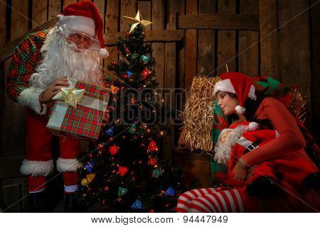 Santa Claus with his sack full of presents and sleeping woman