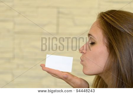 Pretty Young Woman Kissing A Blank Card On Hand