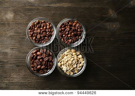 Coffee beans in saucers on wooden background