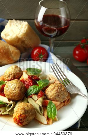 Pasta with meatballs on plate, glass of red wine on wooden  table background
