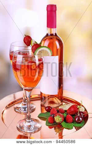 Glasses of wine with strawberries and lime on metal tray on blurred background