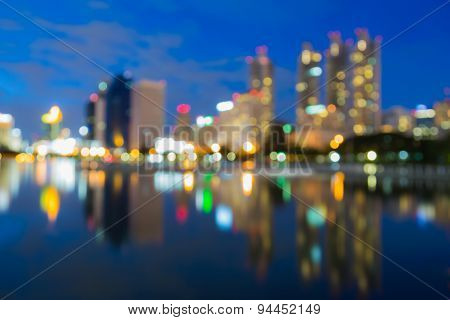 Bokeh city lights during twilight with water reflection