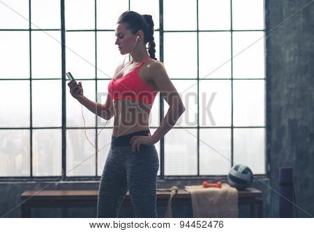 Woman In Profile Listening To Music In Loft Gym