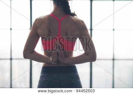 Rear View Of Woman's Hands Clasped Behind Back In Yoga Pose