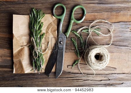Rosemary sprigs on parchment with rope and scissors on wooden background