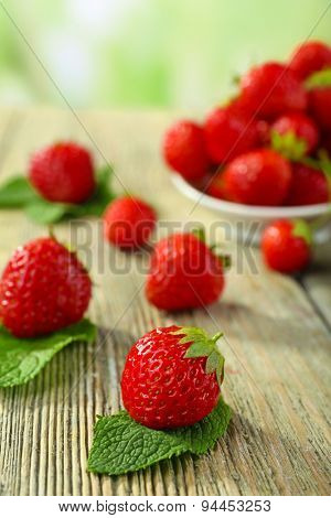 Ripe strawberries in saucer on wooden table on blurred background
