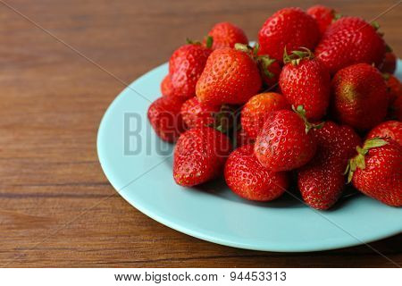 Ripe strawberries in plate on wooden background