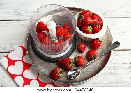 Ripe strawberries in blender on metal tray on wooden table, closeup