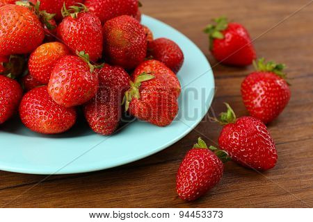Ripe strawberries in plate on wooden table, closeup