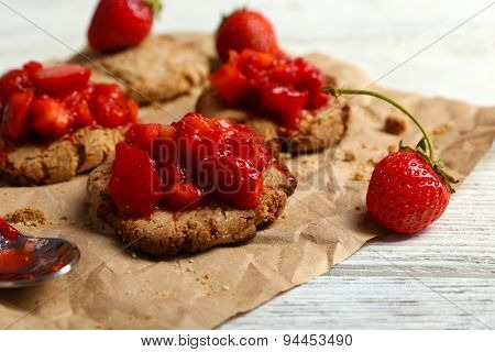 Cookies with fresh strawberry on crumpled parchment on wooden table, closeup