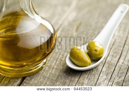green olives and olive oil on old table