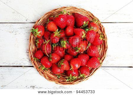 Ripe strawberries in wicker tray, top view