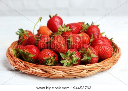 Ripe strawberries in wicker tray on wooden table, closeup