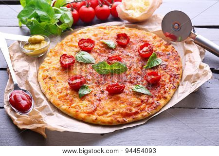 Pizza with basil and cherry tomatoes on parchment on wooden table, closeup