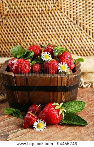 Red ripe strawberries in wooden bucket, on wooden background
