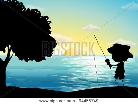 Silhouette boy fishing in the ocean