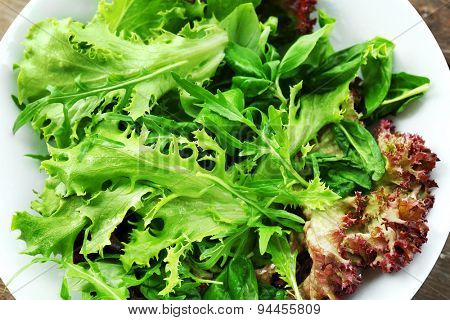 Bowl of mixed green salad on wooden table, closeup