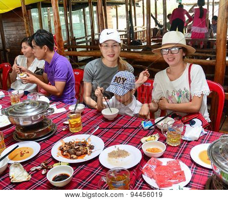 Group Of Unidentified People At A Wooden Restaurant