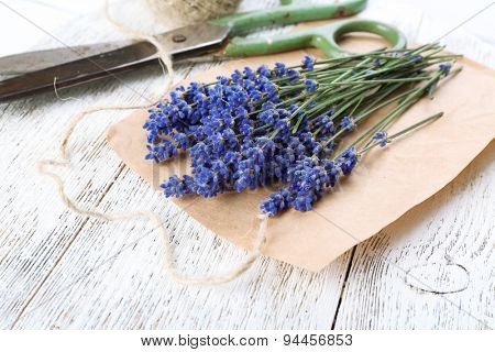 Fresh lavender with rope and scissors on parchment on wooden table, closeup