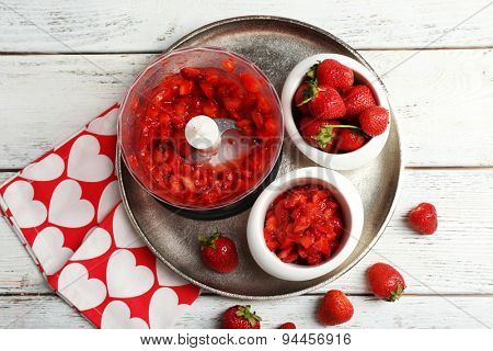 Ripe strawberries in blender on metal tray on wooden table, top view