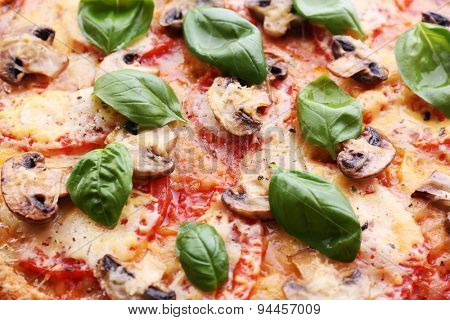 Slice of tasty pizza with vegetables and basil close up