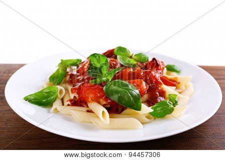 Pasta with tomato sauce and basil on light background