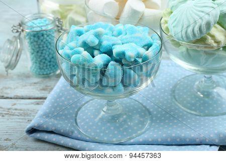 Sweet candies in glassware on napkin, closeup