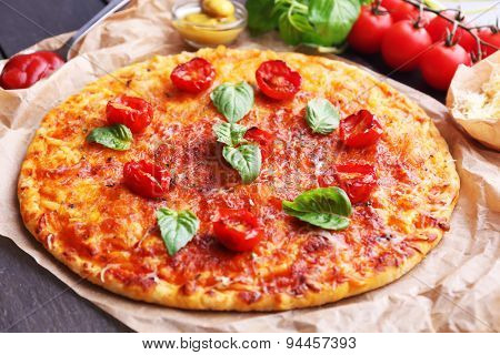 Pizza with basil and cherry tomatoes on parchment, closeup