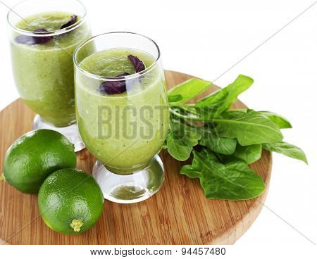 Glasses of green healthy juice with spinach and limes isolated on white
