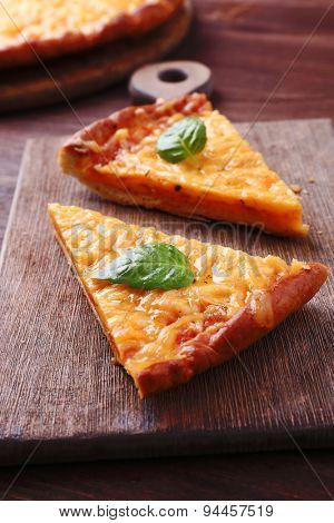 Slices of tasty cheese pizza with basil on table close up