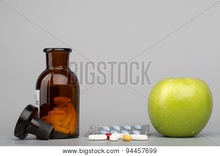 Green apple and colored pills with brown bottle