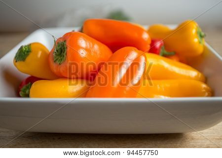Bell Peppers In A Rectangular Dish On A Weathered Wood Background.