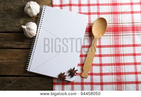 Open recipe book on napkin, on wooden background
