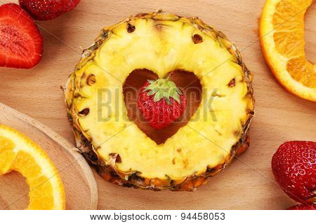Fruits slices with cut in shape of heart and berries on table close up
