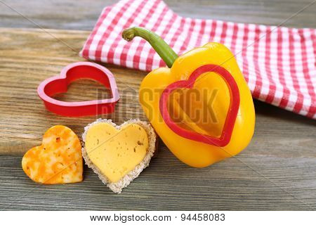 Salad pepper with cut in shape of heart and cheese on table close up